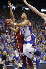 Kansas guard Devon Dotson (1) drives for a basket past Oklahoma guard Alondes Williams (15) during the first half of an NCAA college basketball game in Lawrence, Kan., Saturday, Feb. 15, 2020. (AP Photo/Orlin Wagner)