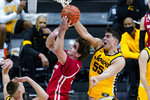 Iowa center Luka Garza (55) blocks the shot of Wisconsin forward Nate Reuvers (35) in the first half of an NCAA college basketball game at the Big Ten Conference men's tournament in Indianapolis, Friday, March 12, 2021. (AP Photo/Michael Conroy)