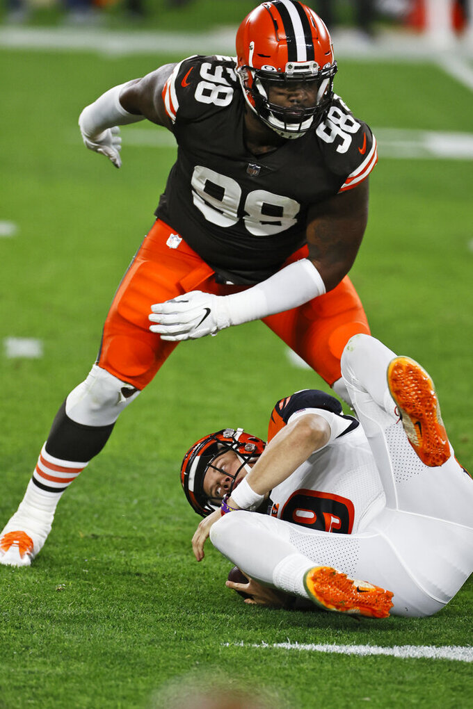 Cleveland Browns defensive tackle Sheldon Richardson (98) sacks Cincinnati Bengals quarterback Joe Burrow during the first half of an NFL football game Thursday, Sept. 17, 2020, in Cleveland. (AP Photo/Ron Schwane)