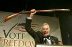 FILE - In this Oct. 21, 2002 file photo, National Rifle Association President Charlton Heston holds up a rifle as he addresses gun owners during a
