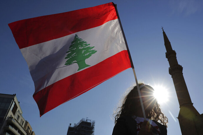 An anti-government protester holds the Lebanese national flag during separate civil parade at the Martyr square, in downtown Beirut, Lebanon, Friday, Nov. 22, 2019. Protesters gathered for their own alternative independence celebrations, converging by early afternoon on Martyrs' square in central Beirut, which used to be the traditional location for the official parade. Protesters have occupied the area, closing it off to traffic since mid-October. (AP Photo/Hassan Ammar)