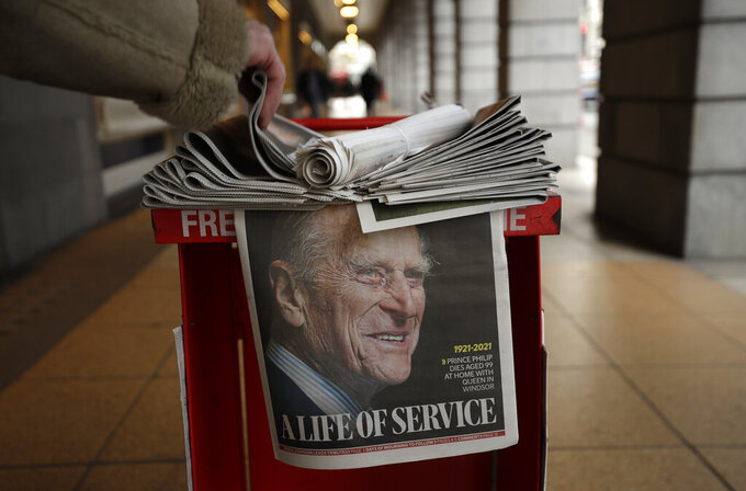 A person takes a copy of a newspaper with a tribute to Britain's Prince Philip on the front page at Leicester Square in London, Friday, April 9, 2021. Buckingham Palace officials say Prince Philip, the husband of Queen Elizabeth II, has died. He was 99. Philip spent a month in hospital earlier this year before being released on March 16 to return to Windsor Castle. (AP Photo/Matt Dunham)