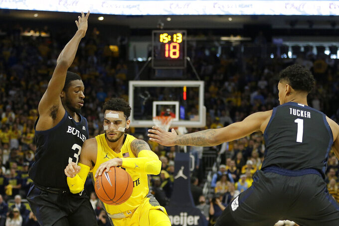 Marquette's Markus Howard drives to the basket between Butler's Kamar Baldwin (3) and Jordan Tucker (1) during the first half of an NCAA college basketball game Sunday, Feb. 9, 2020, in Milwaukee. (AP Photo/Aaron Gash)