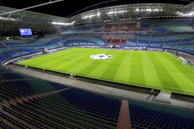 In this Tuesday, March 10, 2020 photo the empty stadium is pictured prior to the Champions League round of 16, 2nd leg soccer match between RB Leipzig and Tottenham Hotspur in Leipzig, Germany. Due to the new coronavirus outbreak several upcoming matches of the German Bundesliga will take place without the attendance of spectators. For most people, the new coronavirus causes only mild or moderate symptoms, such as fever and cough. For some, especially older adults and people with existing health problems, it can cause more severe illness, including pneumonia. (AP Photo/Michael Sohn)