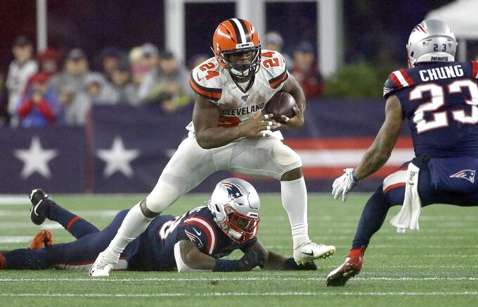 Cleveland Browns running back Nick Chubb, center, carries the ball as New England Patriots safety Patrick Chung, right, defends in the second half of an NFL football game, Sunday, Oct. 27, 2019, in Foxborough, Mass. (AP Photo/Steven Senne)