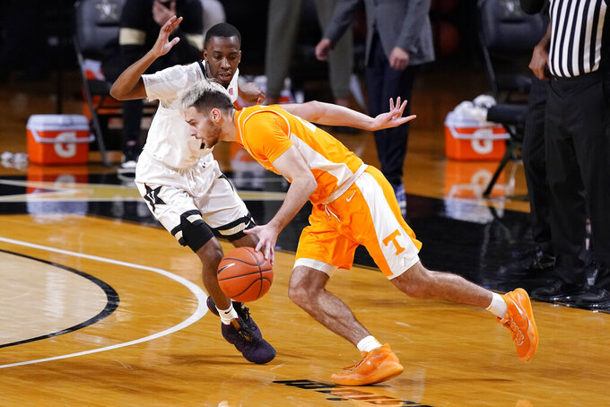 Tennessee's Santiago Vescovi, right, drives against Vanderbilt's Trey Thomas, left, in the first half of an NCAA college basketball game Wednesday, Feb. 24, 2021, in Nashville, Tenn. (AP Photo/Mark Humphrey)