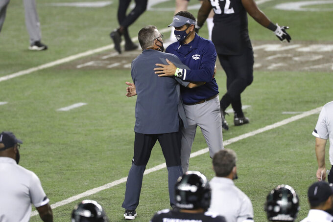 Hawaii coach Todd Graham, left, speaks with Nevada coach Jay Norvell at the end of an NCAA college football game Saturday, Nov. 28, 2020, in Honolulu. Hawaii defeated Nevada 24-21. (AP Photo/Marco Garcia)
