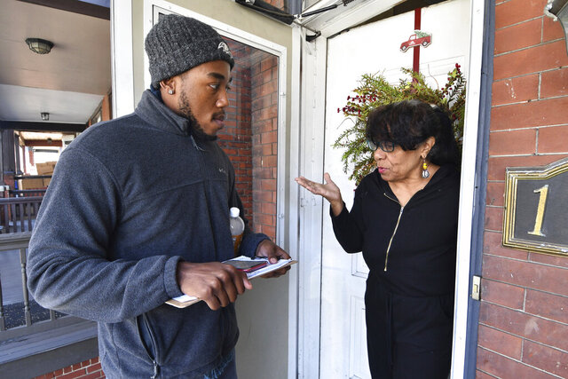 Dom Holmes, a canvasser for Capital Region Stands Up, speaks to a woman at her door as he goes door-to-door asking people to sign a petition for a $15 minimum wage and to come to the organization's meetings, Friday, Feb. 28, 2020 in Harrisburg, Pa. With the 2020 presidential election barreling toward Pennsylvania, grassroots progressive groups that largely rose from deep distress over Donald Trump's 2016 victory are trying to amplify their sway in the battleground state by joining together.  (AP Photo/Marc Levy)