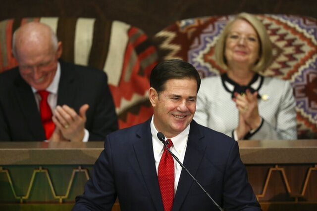 Arizona Republican Gov. Doug Ducey smiles as he pauses during his State of the State address as he talks about Arizona's economy, new jobs, and the state revenue as Senate president Karen Fann, R-Prescott, right, and House Speaker Rusty Bowers, R-Mesa, left, listen in on the opening day of the legislative session at the Capitol Monday, Jan. 13, 2020, in Phoenix. (AP Photo/Ross D. Franklin)