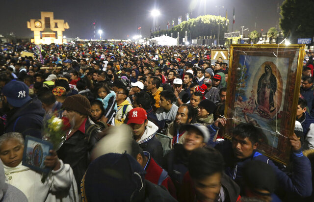 FILE - In this Dec. 12, 2019 file photo, pilgrims arrive at the plaza outside the Basilica of Our Lady of Guadalupe in Mexico City. Due to the COVID-19 pandemic, the Mexican Catholic Church announced on Monday, Nov. 23, 2020 the cancelation of the annual pilgrimage, the largest Catholic pilgrimage worldwide. (AP Photo/Marco Ugarte, File)