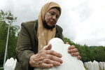 Bida Osmanovic, who lost her son and her mother in Srebrenica massacre, prays at the memorial cemetery in Potocari near Srebrenica, Bosnia, Friday, May 28, 2021. U.N. judges on Tuesday, June 8 deliver their final ruling on the conviction of former Bosnian Serb army chief Radko Mladic on charges of genocide, war crimes and crimes against humanity during Bosnia's 1992-95 ethnic carnage. Nearly three decades after the end of Europe's worst conflict since World War II that killed more than 100,000 people, a U.N. court is set to close the case of the Bosnian War's most notorious figure. (AP Photo/Eldar Emric)
