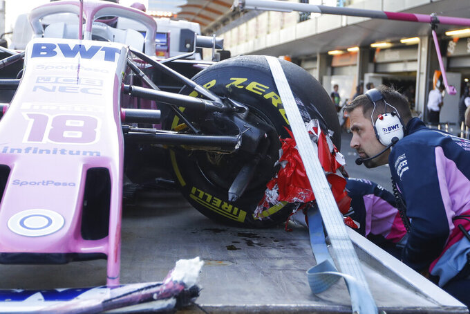 Racing Point team member checks a damaged part of the car of Canada's driver Lance Stroll during the second free practice at the Baku Formula One city circuit in Baku, Azerbaijan, Friday, April 26, 2019. The Azerbaijan F1 Grand Prix race will be held on Sunday. (AP Photo/Sergei Grits)