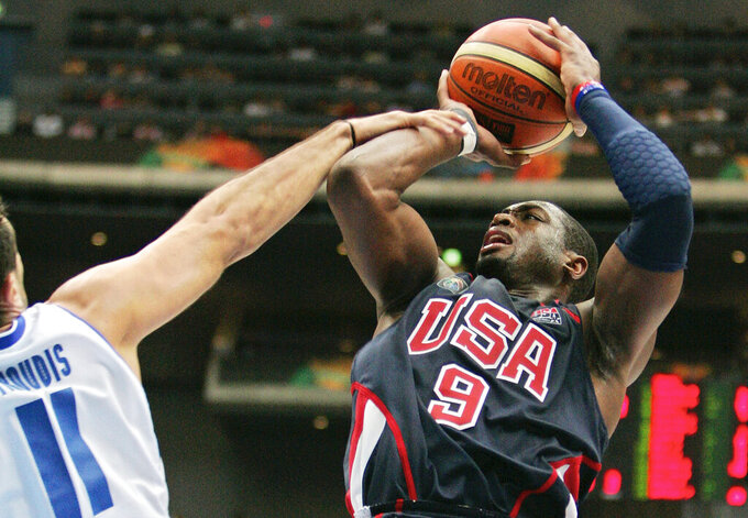 FILE - In this Sept. 1, 2006, file photo, USA's Dwyane Wade (9), right, is fouled by Greece's Dimos Dikoudis during the semifinals of the World Basketball Championships in Saitama, Japan. The 2006 world championship was perhaps the last truly wide-open international basketball event. Argentina arrived as the Olympic champion and Spain left as the world champion, the last time for a long while anyone other than the U.S. would hold either title. (AP Photo/Mark J. Terrill, File)
