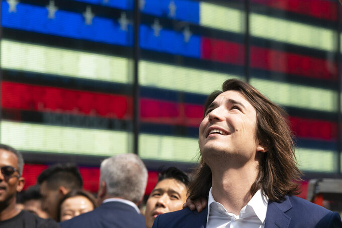 Vladimir Tenev, CEO and co-founder of Robinhood, celebrates in New York's Times Square following his company's IPO, Thursday, July 29, 2021. Robinhood has already changed how people trade stocks and who's doing it. Now its sights are on the rest of the financial industry.(AP Photo/Mark Lennihan)