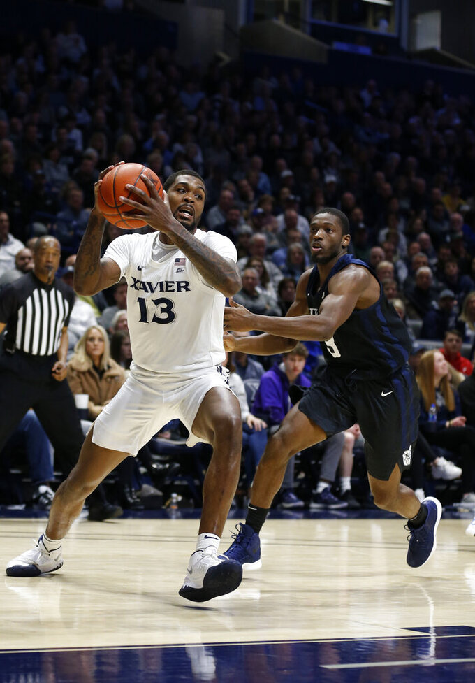 Xavier forward Naji Marshall (13) drives to the basket against Butler guard Kamar Baldwin, right, during the first half of an NCAA college basketball game, Saturday, March 7, 2020, in Cincinnati. (AP Photo/Gary Landers)