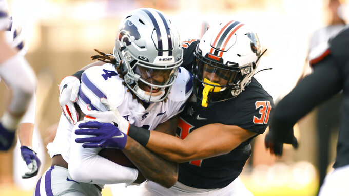 Oklahoma State safety Kolby Harvell-Peel (31) wraps up Kansas State wide receiver Malik Knowles (4) during the first half of an NCAA college football game Saturday, Sept. 25, 2021, in Stillwater, Okla. (AP Photo/Brody Schmidt)