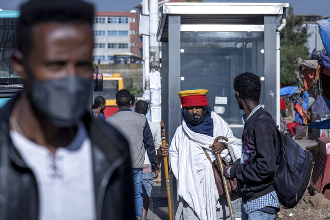 """Passengers walk through a bus station in the capital Addis Ababa, Ethiopia Friday, Nov. 6, 2020. Ethiopia's prime minister says airstrikes have been carried out against the forces of the country's Tigray region, asserting that the strikes in multiple locations """"completely destroyed rockets and other heavy weapons."""" (AP Photo/Mulugeta Ayene)"""