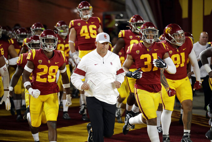 Southern California coach Clay Helton runs onto the field with this team for the start of an NCAA college football game against Arizona on Saturday, Oct. 19, 2019, in Los Angeles. (AP Photo/Marcio Jose Sanchez)