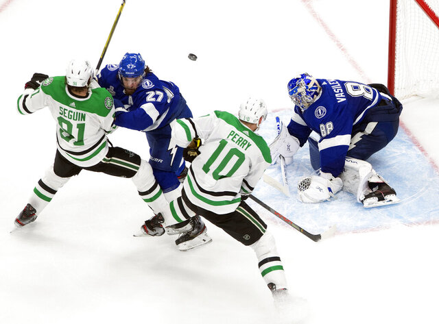 Dallas Stars' Tyler Seguin (91) and Corey Perry (10) battle Tampa Bay Lightning's Ryan McDonagh (27) as Lightning goalie Andrei Vasilevskiy (88) makes a save during third-period NHL Stanley Cup finals hockey action in Edmonton, Alberta, Monday, Sept. 21, 2020. (Jason Franson/The Canadian Press via AP)