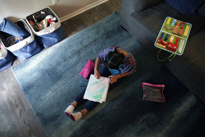 Felicity Brown, 9, draws as she takes a break from math practice at her home in Austin, Texas, Tuesday, July 13, 2021. After homeschooling during the pandemic, the Brown family have switched to homeschooling their kids permanently using a Catholic-based curriculum and won't be sending them back to in-person schools this fall. (AP Photo/Eric Gay)