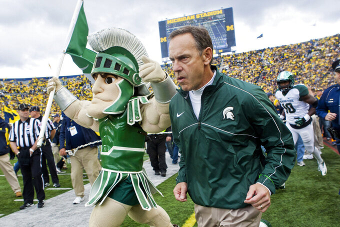 FILE - In this Oct. 20, 2012, file photo, Michigan State head coach Mark Dantonio, right, runs out on to the Michigan Stadium field alongside the school mascot, Sparty, before an NCAA college football game with Michigan in Ann Arbor, Mich. Dantonio announced his retirement Tuesday, Feb. 4, 2020, ending a 13-year run in which he guided the Spartans to heights they hadn't reached in decades.   (AP Photo/Tony Ding, File)