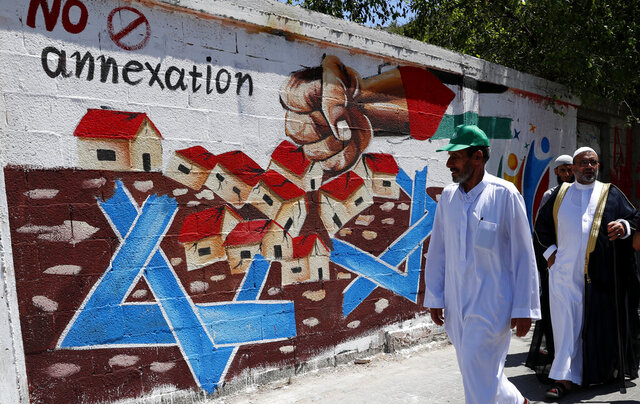 Hamas supporters pass a mural against Israel's plan to annex parts of the West Bank and U.S. President Donald Trump's mideast initiative, after Friday prayer's protest at the main road of Rafah refugee camp, Gaza Strip, Friday, July 3, 2020. (AP Photo/Adel Hana)