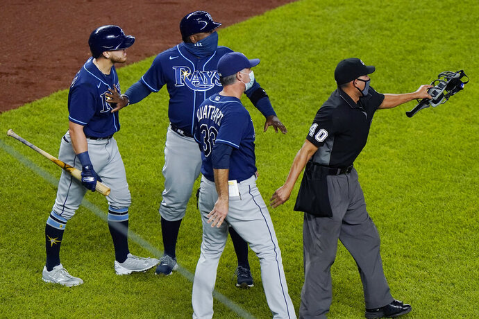 FILE - In this Sept. 1, 2020, file photo, Tampa Bay Rays pinch-hitter Michael Brosseau, left, is restrained by a coach as second base umpire Chad Fairchild (4) warns New York Yankees relief pitcher Aroldis Chapman to stay away from Brosseau as the two players exchanged words following the Rays' 5-3 loss to the Yankees in a baseball game at Yankee Stadium in New York. The altercation started after Chapman threw a high pitch at Brosseau. The Rays wear blue T-shirts with four horses lined up behind a fence, a reference to Tampa Bay manager Kevin Cash declaring