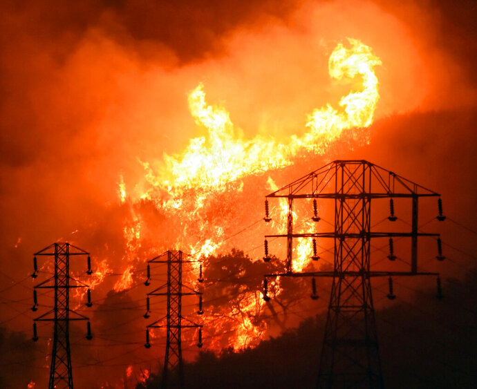 FILE - In this Dec. 16, 2017, file photo provided by the Santa Barbara County Fire Department, flames burn near power lines in Sycamore Canyon near West Mountain Drive in Montecito, Calif. A federal judge approved Pacific Gas & Electric Corp.'s plans Tuesday, April 23, 2019, to pay $235 million in employee bonuses this year, despite the California utility's bankruptcy and objections from lawyers of victims of the state's massive wildfires. (Mike Eliason/Santa Barbara County Fire Department via AP, File)