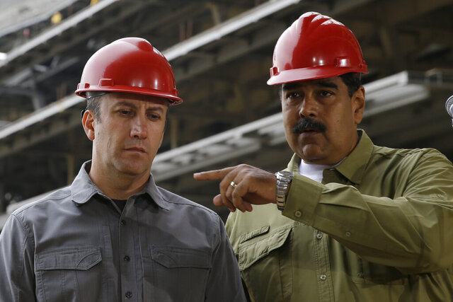 FILE - In this May 19, 2018 file photo, Venezuela's President Nicolas Maduro, right, and Vice President Tareck El Aissami tour La Rinconada baseball stadium that is under construction on the outskirts of Caracas, Venezuela. On Thursday, March 26, 2020, the U.S. Justice Department made public it has charged in several indictments against Maduro and his inner circle, including El Aissami, that the leader has effectively converted Venezuela into a criminal enterprise at the service of drug traffickers and terrorist groups as he and his allies stole billions from the South American country. (AP Photo/Ricardo Mazalan, File)