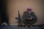 A U.S.-backed Syrian Democratic Forces (SDF) fighter sits inside a building used as a temporary base near the last land still held by Islamic State militants in Baghouz, Syria, Monday, Feb. 18, 2019. Hundreds of Islamic State militants are surrounded in a tiny area in eastern Syria are refusing to surrender and are trying to negotiate an exit, Syrian activists and a person close to the negotiations said Monday. (AP Photo/Felipe Dana)