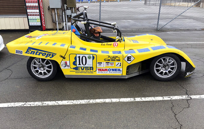 In this April 5, 2019 photo, a driver sits in an all-electric single-seat race car that competed in the Green Grand Prix, a fuel mileage rally for alternate-fuel vehicles and hybrids at Watkins Glen International in Watkins Glen, N.Y. It is the only event of its kind in the United States sanctioned and insured by the Sports Car Club of America and just celebrated its 15th anniversary. (AP Photo/John Kekis)