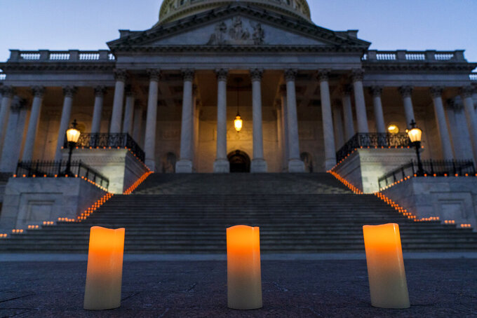 Electric candles await a bipartisan group of members Congress for a moment of silence honoring the 500,000 U.S. COVID-19 deaths, Tuesday, Feb. 23, 2021, by the east front steps of the Capitol in Washington. (AP Photo/Jacquelyn Martin)