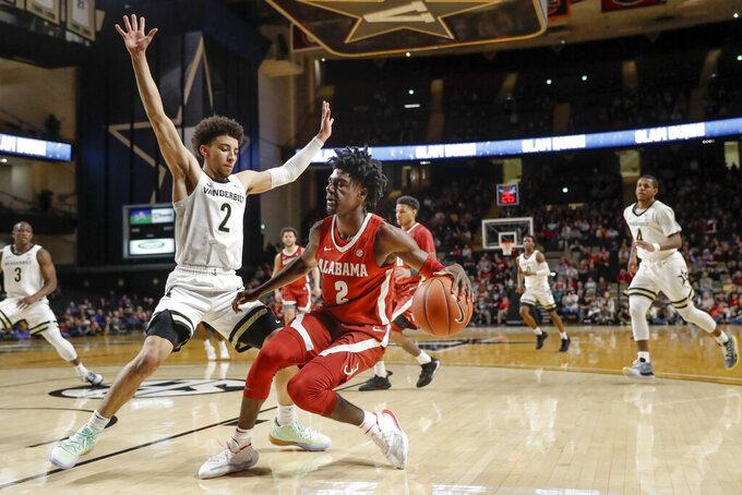 Alabama's Kira Lewis Jr., center, drives against Vanderbilt's Scotty Pippen Jr., left, in the first half of an NCAA college basketball game Wednesday, Jan. 22, 2020, in Nashville, Tenn. (AP Photo/Mark Humphrey)
