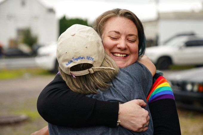 Alisha Hoffman-Mirilovich, right, and Claudia Glennan embrace at the Edwardsville Pierogi Festival in Edwardsville, Pa., Friday, June 11, 2021. (AP Photo/Matt Rourke)