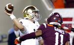 Notre Dame quarterback Ian Book, left, throws a pass as defensive lineman Houshun Gaines (11) closes in during the first half of an NCAA college football game in Blacksburg, Va., Saturday, Oct. 6, 2018. (AP Photo/Steve Helber)