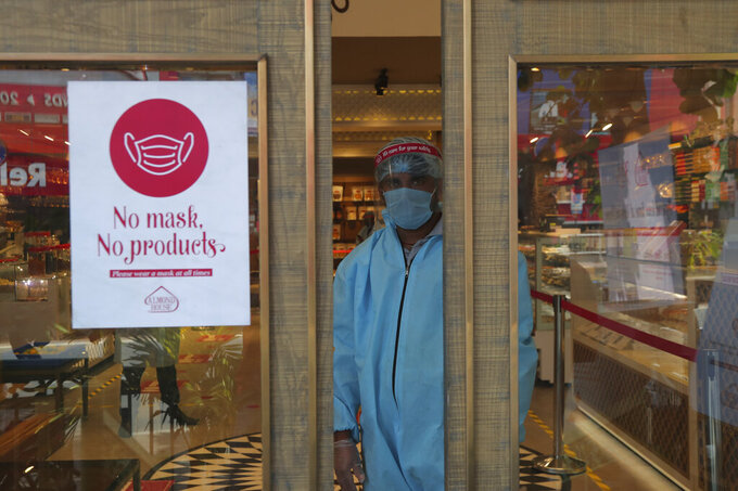 An Indian security personnel wearing protective gear stands by the entrance of a sweet shop in Hyderabad, India, Friday, June 5, 2020. The more than two-month-old lockdown is now largely being enforced only in high-risk areas, known as containment zones. The government has partially restored train service and domestic flights and allowed the reopening of shops and manufacturing. (AP Photo/Mahesh Kumar A.)