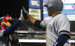 New York Yankees' Didi Gregorius receives a high-five and a stuffed parrot, left, at the dugout following his solo home run off Minnesota Twins' Devin Smeltzer in the ninth inning of a baseball game, Wednesday, July 24, 2019, in Minneapolis. Gregorius had three RBIs. The Yankees won 10-7. (AP Photo/Jim Mone)