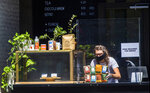 A barista sets bags of coffee behind a plexiglass barrier at a counter set outdoors of Stumptown Coffee Roasters downtown Los Angeles Thursday, May 21, 2020. A posted sign reads: