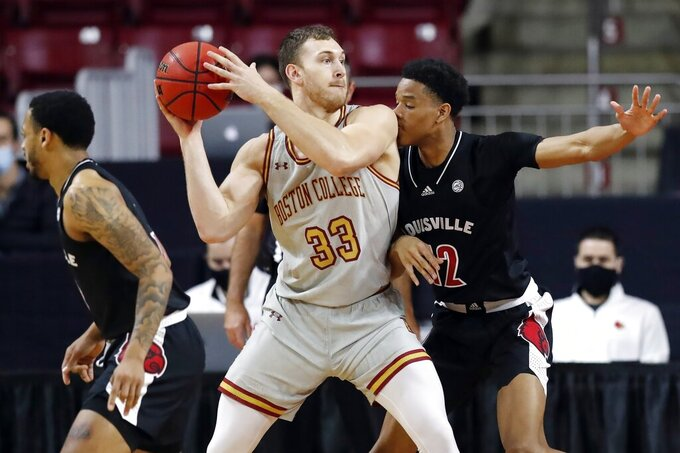 Louisville's J.J. Traynor (12) defends against Boston College's James Karnik (33) during the first half of an NCAA college basketball game, Saturday, Jan. 2, 2021, in Boston. (AP Photo/Michael Dwyer)
