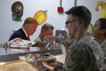 President Donald Trump, left, serves dinner accompanied by Joint Chiefs Chairman Gen. Mark Milley, center, during a surprise Thanksgiving Day visit to the troops, Thursday, Nov. 28, 2019, at Bagram Air Field, Afghanistan. (AP Photo/Alex Brandon)