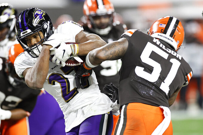 Baltimore Ravens running back J.K. Dobbins (27) rushes for a one-yard touchdown against Cleveland Browns linebacker Mack Wilson (51) during the second half of an NFL football, Monday, Dec. 14, 2020, in Cleveland. (AP Photo/Ron Schwane)