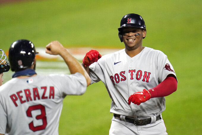 Boston Red Sox's Rafael Devers, right, is greeted near home plate by Jose Peraza (3) after Devers hit a three-run home run off Baltimore Orioles relief pitcher Jorge Lopez during the fifth inning of a baseball game, Friday, Aug. 21, 2020, in Baltimore. Red Sox's Kevin Pillar, not visible, and Peraza scored on the home run. (AP Photo/Julio Cortez)