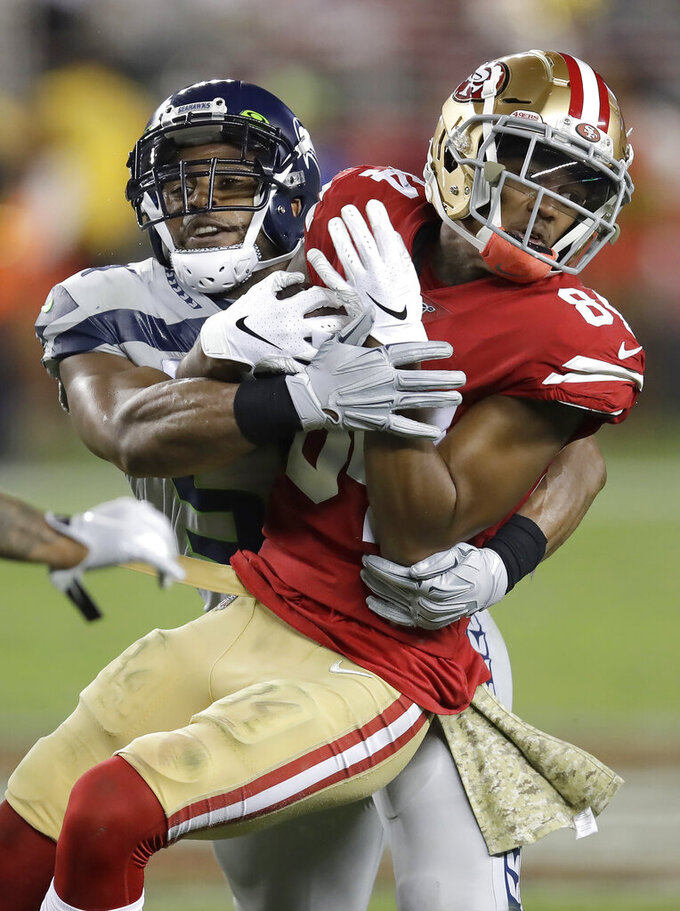 San Francisco 49ers wide receiver Kendrick Bourne (84) is tackled by Seattle Seahawks middle linebacker Bobby Wagner during the first half of an NFL football game in Santa Clara, Calif., Monday, Nov. 11, 2019. (AP Photo/Ben Margot)