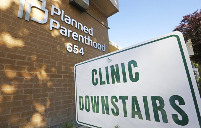 FILE - In this Aug. 21, 2019, file photo, a sign is displayed at Planned Parenthood of Utah in Salt Lake City.  The Biden administration is beginning to undo a Trump-era ban on clinics referring women for abortions, a policy directive that led to Planned Parenthood leaving the federal family planning program.    (AP Photo/Rick Bowmer)