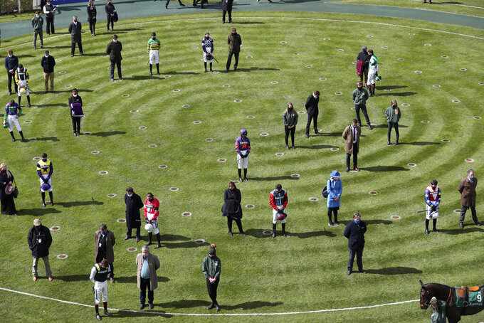 Jockey, owners and trainers stand in the parade ring during the two minute silence before the first race on the third day of the Grand National Horse Racing meeting at Aintree racecourse, near Liverpool, England, Saturday April 10, 2021. (AP Photo/Scott Heppell, Pool)