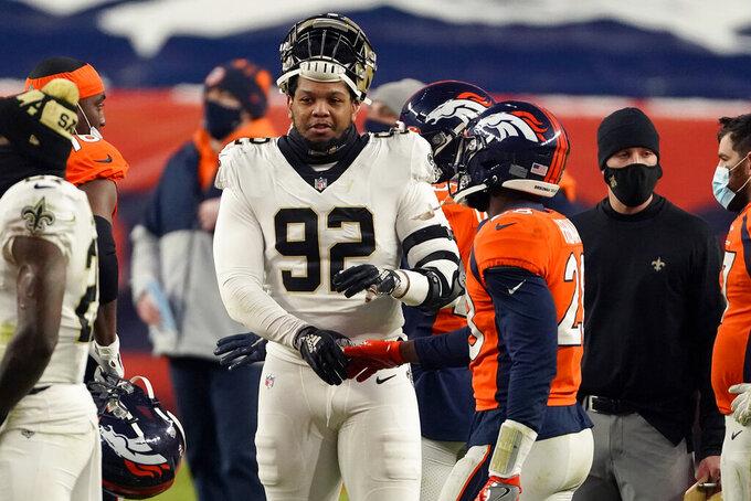 New Orleans Saints defensive end Marcus Davenport (92) greets Denver Broncos running back Royce Freeman after an NFL football game, Sunday, Nov. 29, 2020, in Denver. The Saints won 31-3. (AP Photo/Jack Dempsey)