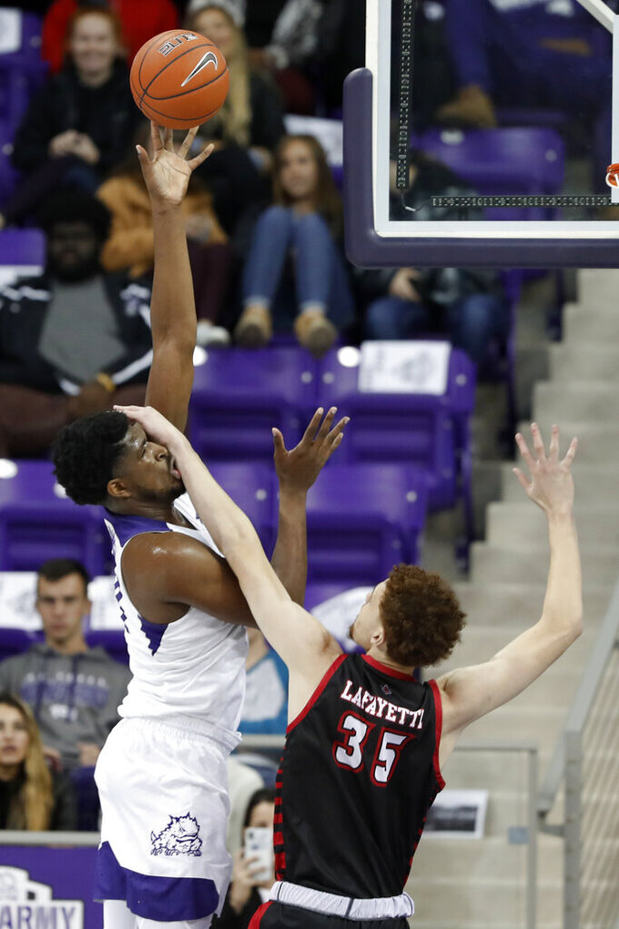 TCU center Kevin Samuel (21) takes a hand to the face from Louisiana-Lafayette forward Kristian Lafayette (35) while attempting a shot during the first half of an NCAA college basketball game in Fort Worth, Texas, Tuesday, Nov. 12, 2019. (AP Photo/Tony Gutierrez)