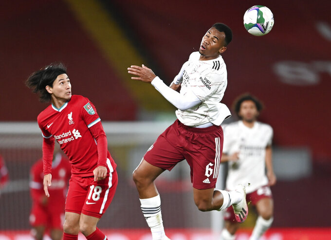 Liverpool's Takumi Minamino, left, watches as Arsenal's Gabriel heads the ball during the English League Cup fourth round soccer match between Liverpool and Arsenal at Anfield, Liverpool, England, Thursday, Oct. 1, 2020. (Laurence Griffiths/Pool via AP)