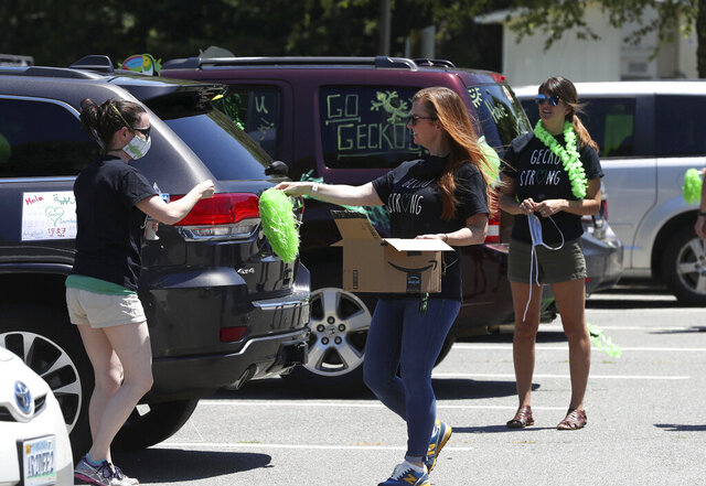 In this June 8, 2020, photo, Greer Elementary School teachers decorate their cars before a parade to visit students from a safe distance during the coronavirus pandemic in Charlottesville, Va. Dozens of teachers participated in the event. (Andrew Shurtleff/The Daily Progress via AP)