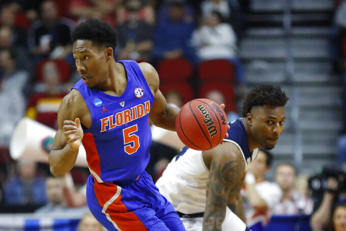 Florida guard KeVaughn Allen drives up court ahead of Nevada forward Jordan Caroline, right, during a first round men's college basketball game in the NCAA Tournament, Thursday, March 21, 2019, in Des Moines, Iowa. (AP Photo/Charlie Neibergall)